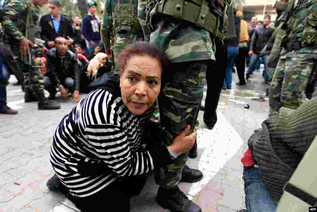 January 20: A Tunisian protester grabs hold of a soldier's leg for safety as shots are fired in the air in front of the headquarters of the Constitutional Democratic Rally (RCD) party of ousted president Zine al-Abidine Ben Ali in downtown Tunis. (Reuters
