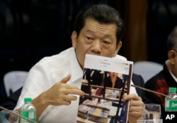 Kam Sin Wong, a Chinese junket operator in the Philippines, presents a photo as hearings into how about $81 million of Bangladesh's stolen funds were transmitted online to four private accounts at a branch of the Rizal Commercial Banking Corp. are held.