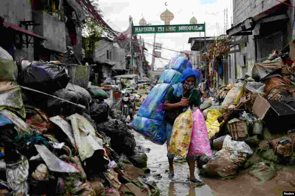 A man selling pillows and mattresses walks past debris from the flood brought by Typhoon Vamco, in Marikina, Metro Manila, Philippines.