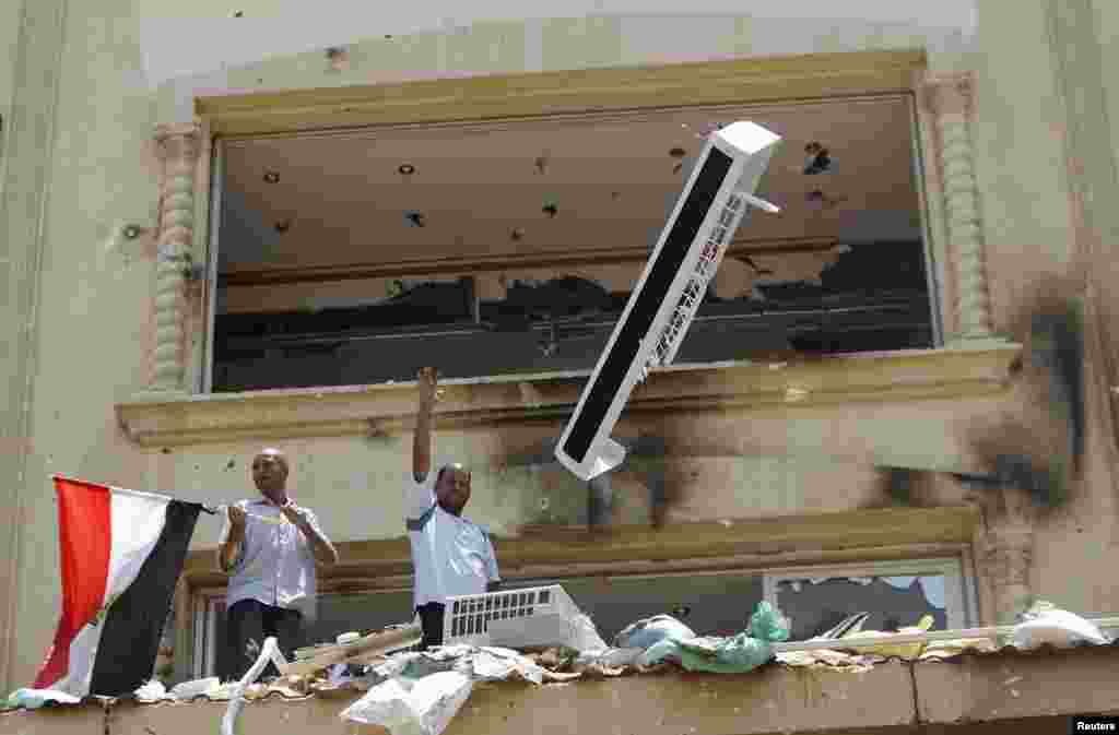 A looter gestures as part of an air-conditioning is thrown down from the Muslim Brotherhood's headquarters after it was burned down by protesters opposing Egyptian President Mohamed Mursi in Cairo's Moqattam district July 1, 2013.