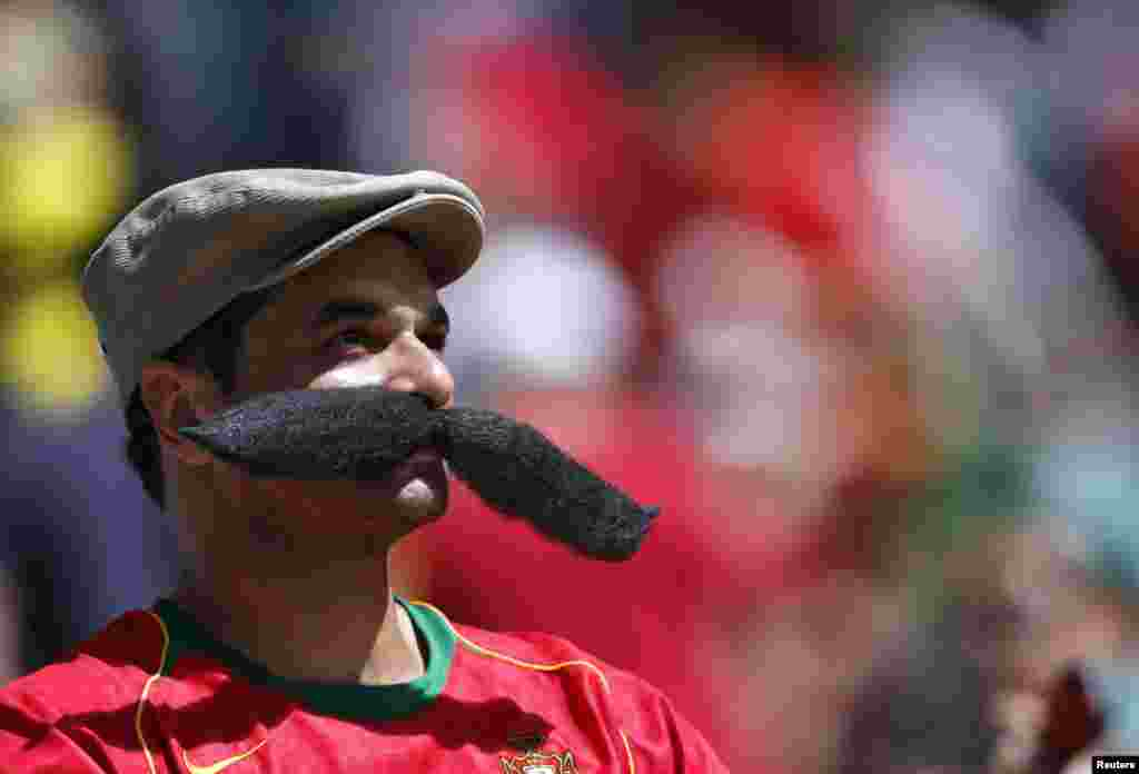 A fan of Portugal watches his team play against Germany during the 2014 World Cup Group G soccer match at the Fonte Nova arena in Salvador, Brazil.