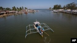 一艘漁船回航他們在菲律賓北部三描禮士省馬辛洛克鎮的村子(2013年5月7日檔案照片)