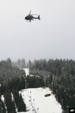 Warm temperatures forced organizers to truck and airlift snow to the venue. Here, hay is dropped on Cypress Mountain, scene of freestyle skiing and snowboarding events.