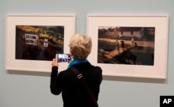 """In this March 15, 2018, photo, a woman views a pair of Paul Fusco photographs that are part of the exhibit, """"The Train: RFK's Last Journey,"""" at the San Francisco Museum of Modern Art in San Francisco."""
