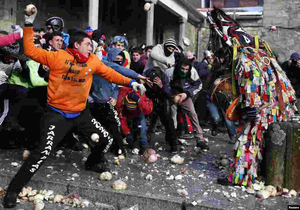 Revelers throw turnips at the Jarramplas as he makes his way through the streets while beating his drum during the Jarramplas traditional festival in Piornal, southwestern Spain.