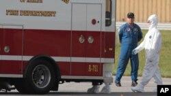 Un médico estadounidense expuesto al virus del ébola llega caminando a una ambulancia en el aeropuerto de Frederick, al norte de Maryland.