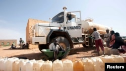 FILE - Boys from the Kassab camp for Internally Displaced Persons (IDP) collect water in Kutum, North Darfur.