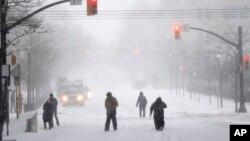 Les gens marchent sur une route couverte de neige pendant la tempête de neige, à Jersey City, NJ, 23 janvier 2016.