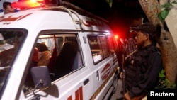 A policeman stands as one of the ambulances carrying bodies, which according to Edhi Foundation's rescue workers were the 13 picnickers who drowned at Hawks Bay beach and were later recovered, arrive outside the hospital morgue in Karachi, Pakistan Septem
