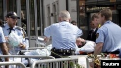 Medical personnel evacuate a man who set himself on fire outside the courthouse where Norwegian mass killer Anders Behring Breivik is on trial for murdering 77 people last July, Oslo, May 15, 2012.