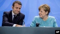 Presiden Prancis Emmanuel Macron (kiri) dan Kanselir Jerman Angela Merkel (kanan) menghadiri konferensi pers seusai pertemuan menjelang KTT G-20 di Berlin, Jerman, Kamis, 29 Juni 2017. (Michael Kappeler / dpa via AP)