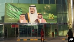 FILE - Images of King Salman, center, Crown Prince Mohammed bin Nayef, left, and Deputy Crown Prince Mohammed bin Salman hang at the entrance of a shopping center in Riyadh, Saudi Arabia, Dec. 14, 2015.