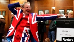 Ekspresi seorang penduduk kepulauan Falkland saat memasukkan surat suaranya ke dalam kotak di TPS Stanley (10/3).