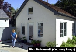 "FILE: Christine Minnehan sweeps up in front of her ""granny flat"" located in the backyard of her Sacramento, Calif home. It is an example of second homes property owners can rent to others. June 27, 2002."