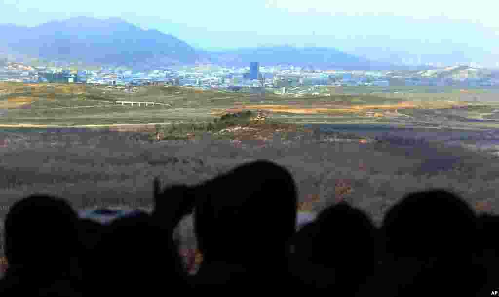 参观人士2013年4月9日在韩国坡州板门店村边境非军事区附近的多拉观测站用望远镜观看朝鲜开城的联合工业区。