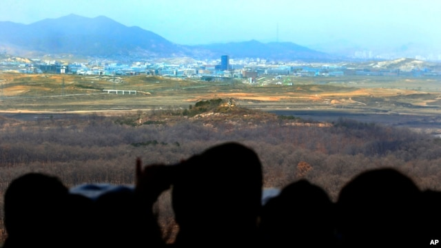 Visitors look at the industrial complex in Kaesong, North Korea, through binoculars at Dora Observation Post in the demilitarized zone (DMZ) near the border village of Panmunjom, in Paju, South Korea, April 9, 2013.