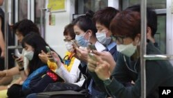 Passengers wear masks as a precaution against Middle East Respiratory Syndrome (MERS) as they use their smartphones on a subway train in Seoul, South Korea, Monday, June 8, 2015.