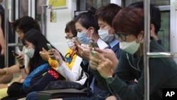 Putnici sa maskama u podzemnoj železnici u Seulu