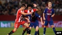 L'attaquant Lionel Messi, au centre, en duel avec les milieux de terrain de Gérone, Pere Pons, à gauche, et Alex Granell lors du match de football entre le FC Gérone et le FC Barcelone au stade Montilivi de Gérone le 23 septembre 2017.