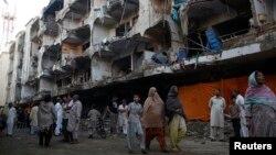 巴基斯坦最大城市卡拉奇3月4 日在一座清真寺外發生汽車炸彈事件﹐附近居民在一座損毀得建築物前視察情況。