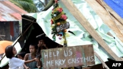 Children around a makeshift shelter beside a message on a board, next to a Christmas tree on a street in Basay, Samar province, Nov. 28, 2013.