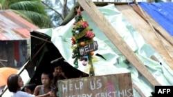 临时栖身处里的菲律宾儿童。简易圣诞树上挂的牌子上写着:美国帮忙 圣诞快乐