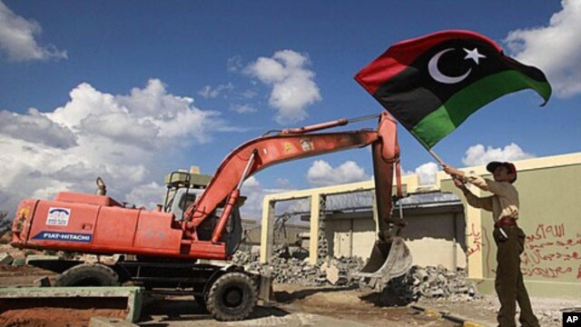 A boy waves a Kingdom of Libya flag as a bulldozer demolishes walls of the residence of Moammar Gadhafi at the Bab al-Aziziyah complex in Tripoli, October 16, 2011.