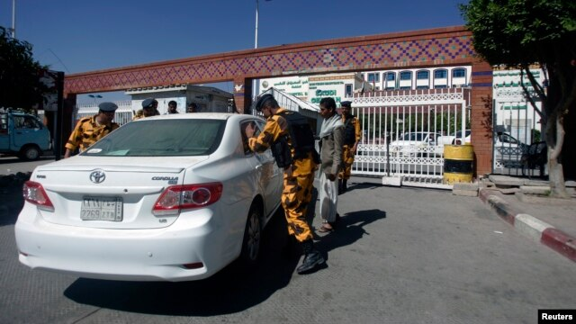 Police troopers check a car at the gate of a hospital where a Japanese diplomat is being treated in Sana'a, Dec. 15, 2013.