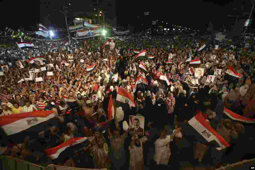 Supporters of ousted Egypt's President Mohamed Morsi hold his portraits and wave Egyptian flags as they shout slogans during a demonstration after the Iftar prayer in Nasr City, Cairo, July 10, 2013.