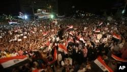 被推翻的埃及總統穆爾西的支持者在開羅納塞爾城開齋祈禱後的示威活動中手持穆爾西肖像,揮舞埃及國旗,並呼喊口號。
