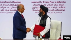 Mullah Abdul Ghani Garadar, lider talibanske delegacije i Zalmay Khalilzad, američki mirovni izaslanik u Afganistanu rukuju se poslije potpisivanja sporazuma u Dohi u Kataru, 29. feburara 2020.