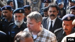Polisi Pakistan mengawal diplomat AS, Raymond Davis menuju pengadilan di kota Lahore. Davis diadili atas tuduhan melakukan pembunuhan.