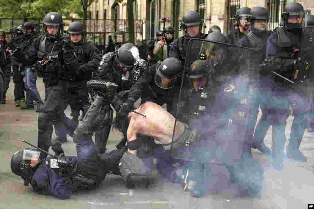 Riot police officers detain a man during a demonstration against a labor law bill in Paris, France.