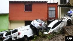 Mobil yang tersapu saat banjir yang dipicu oleh Badai Tropis Cristobal, terlihat tumpang tindih di Panchimalco, El Salvador, 3 Juni 2020.