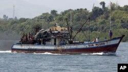 Filipino fishermen wave from a fishing boat bound to fish near Scarborough Shoal in Masinloc, Zambales May 10, 2012.