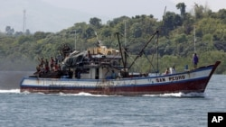 Filipino fishermen wave from a fishing boat bound to fish near Scarborough Shoal in Masinloc, Zambales May 10, 2012.