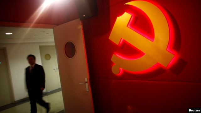 A trainee walks pass a communist party logo as he attends a training course at the communist party school called China Executive Leadership Academy, Sept. 2012.