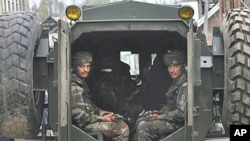 Indian Army soldiers look from inside of an armored vehicle near the site of a gun battle on the outskirts of Srinagar (File 2010)