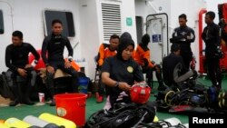 A group of divers prepares their gear on the deck of the Search and Rescue (SAR) ship KN Purworejo during a search operation for passengers onboard AirAsia Flight 8501 in the Java Sea, Jan. 4, 2015.