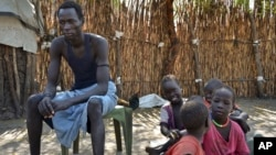 FILE - A South Sudanese man, who says he was shot in the back and thigh by government soldiers while trying to get food in a nearby town in order to feed his starving family, sits with his five children outside his house in Jiech, Ayod County, South Sudan