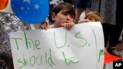 Shua Rich, de 6 años de edad, sostiene su letrero mientras protesta con su madre durante una manifestación contra las políticas de inmigración de EE. UU. frente a una oficina del representante Kevin Yoder, junio 22, 2018, en Overland Park, Kansas.