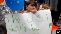 """Šestogodišnji Šua Rič drži natpis na kojem piše """"SAD bi trebalo da budu fine"""" tokom protesta zbog imigracione politike SAD, ispred kancelarije kongresmena Kevina Jodera u Kanzasu, 22. juna 2018."""