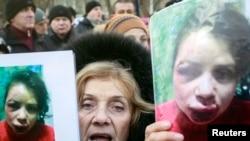 抗议者手举车娜沃尔的照片。记者车娜沃尔发表有关高层政府官员资产的报道后被毒打。2013年12月26日