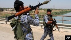 Iraqi federal policemen patrol in the town of Taji, about 20 kilometers north of Baghdad, Iraq. (File)