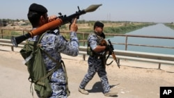 Iraqi federal policemen patrol in the town of Taji, about 20 kilometers (12 miles) north of Baghdad, June 26, 2014.