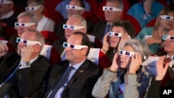French National Centre for Space Studies (CNES) president Jean-Yves Le Gall, left, French President Francois Hollande, center, and former French minister and astronaut Claudie Haignere, right, wear 3D glasses as they visit the Cite des Sciences at La Villette during a broadcast of the Rosetta mission as it orbits around comet 67/P Churyumov-Gersimenko in Paris, Wednesday, Nov. 12, 2014. Hundreds of millions of miles from Earth, a European spacecraft made history Wednesday by successfully landing on the icy, dusty surface of a speeding comet — an audacious first designed to answer big questions about the universe. (AP Photo/Jacques Brinon, Pool)