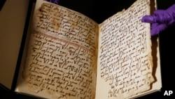 Seorang staf universitas menunjukkan halaman Al Quran tertua yang pernah ditemukan, di Universitas Birmingham, di kota Birmingham, Inggris (foto: AP).