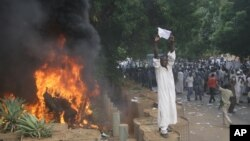 A Sudanese protester stands on a barricade during a demonstration in Khartoum, September 14, 2012, as part of widespread anger across the Muslim world about a film ridiculing Islam's Prophet Muhammad.