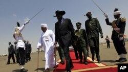 South Sudanese President Salva Kiir, center, walks with Sudanese counterpart Omar al-Bashir, Khartoum, Oct. 2011 (file photo).