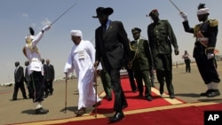 South Sudanese President Salva Kiir (C) walks with his Sudanese counterpart Omar al-Bashir (in white) before Kiir's departure from Khartoum, October 9, 2011.